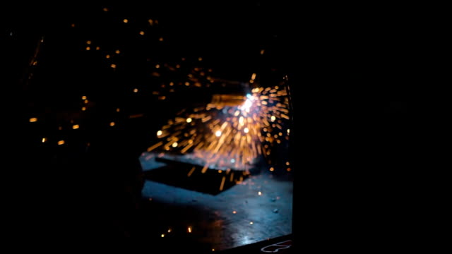 Worker weld of the metal structures in the dark. Sparks fly nicely on around video