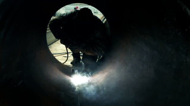 stockvideo's en b-roll-footage met worker welding metal piping - lassen