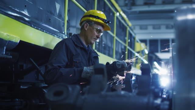 vídeos de stock, filmes e b-roll de trabalhador com moedor de ângulo faz metalworking em ambiente industrial - transporte ferroviário