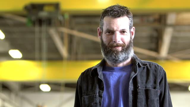 vídeos de stock e filmes b-roll de worker with beard standing in warehouse - homem casual standing sorrir