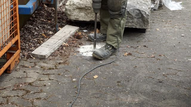 a worker with fixed safety shoes uses a spindle drill to drill through a concrete block on a firmly sealed paving slab. - камень стоковые видео и кадры b-roll