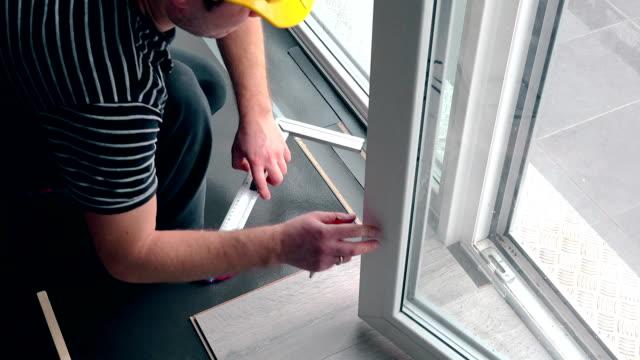 arbetare med penna gör markeringar på laminatgolv ombord - reparera bildbanksvideor och videomaterial från bakom kulisserna