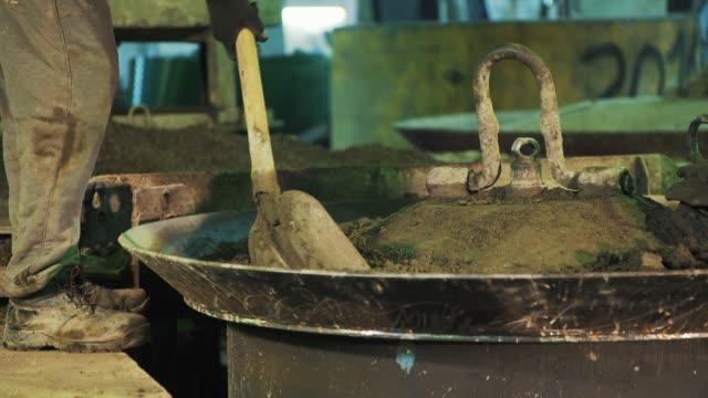 金属釜の蓋の上のセメント粒子を振動シャベル dig でワーカー - セメント点の映像素材/bロール