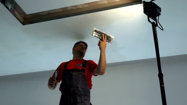 worker with spatula apply filler on plasterboard ceiling. Niche for lighting
