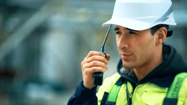 vídeos de stock, filmes e b-roll de trabalhador com walkie talkie e equipamento de segurança na fábrica indusrial - gasolina