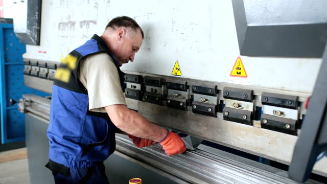 Worker works with a press for processing metal billets. Worker bends a metal workpiece on a large press. production line worker stock videos & royalty-free footage
