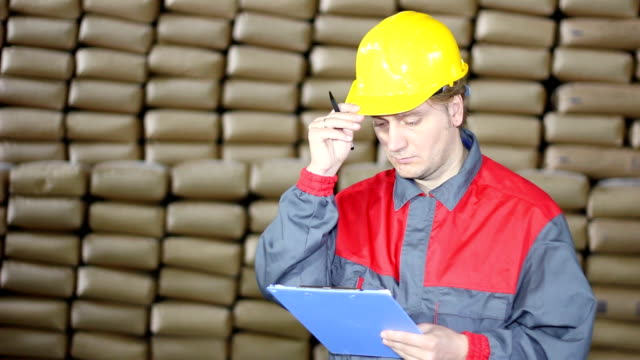 Worker writing on clipboard in Warehouse video