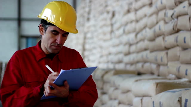 Worker Writing on Clipboard Warehouse worker with clipboard checking inventory.  cement stock videos & royalty-free footage