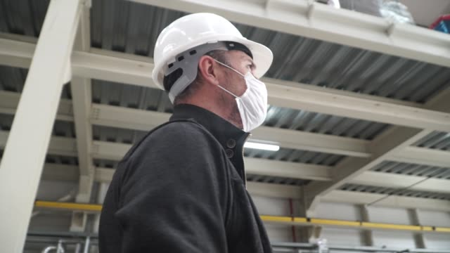 worker/engineer wearing disposal face mask for protect dust smoke and corona virus while working in workplace or factory - covid-19 filmów i materiałów b-roll