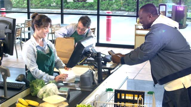 スーパーマーケットのチェックアウト時の作業者と顧客 - disabilitycollection点の映像素材/bロール