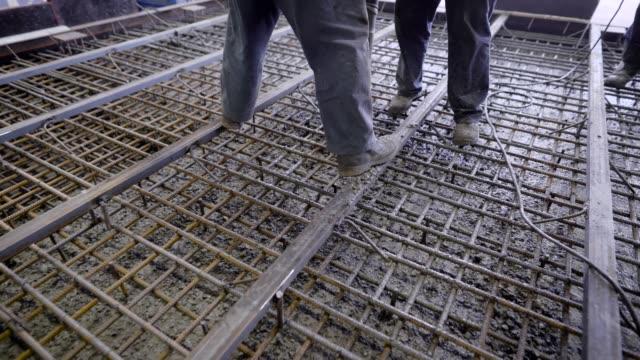 労働者およびエンジニアの流し込み。コンクリートと鉄筋のトン固体モノリシック化合物を形成します。 - 支えられた点の映像素材/bロール