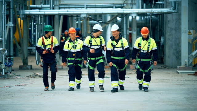 Workers and engineers walking at industrial factory video