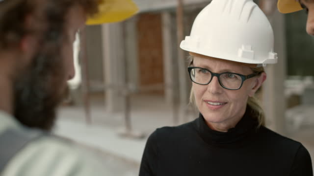 workers and their foreman discussing plan details with the female architect outside at the construction site - leanincollection stock videos & royalty-free footage