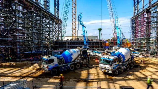 рабочие и руководство грузовика или заливки бетона на структуру строительной площадки электростанции - бетон стоковые видео и кадры b-roll