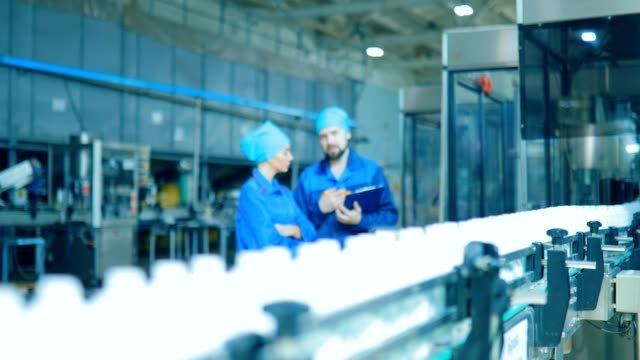 arbetstagare bygger bredvid raden transportband. kontrollera produktionen på rad - livsmedelstillverkningsfabrik bildbanksvideor och videomaterial från bakom kulisserna