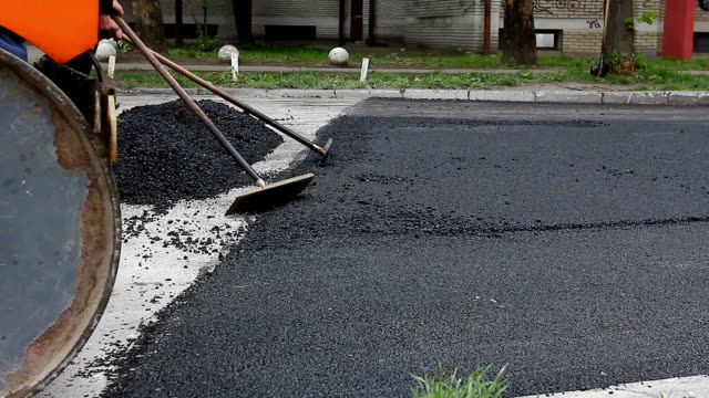 Workers are leveling hot asphalt after is applied on the ground, road works video