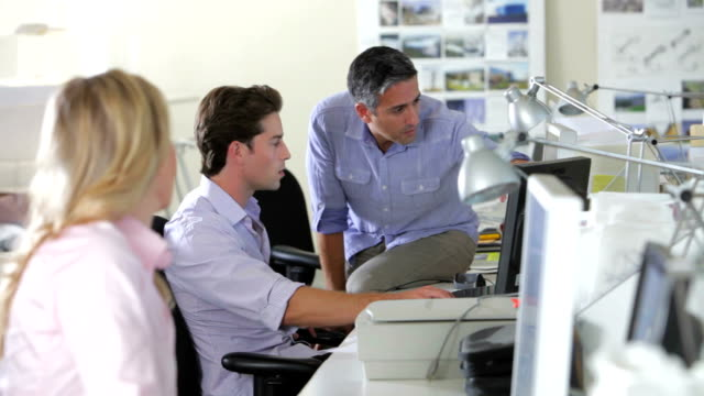 Workers At Desks In Busy Creative Office video
