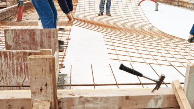 ds workers at the building site placing a steel wire mesh on the ground - inarcare la schiena video stock e b–roll