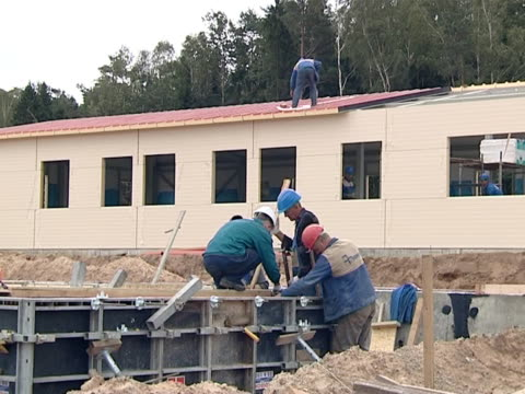 workers concrete foundations and roof house. video