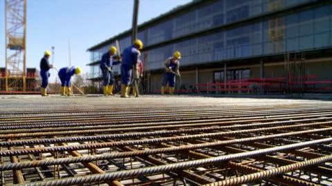 lavoratori dirigere concrete per la realizzazione del sito - calcestruzzo video stock e b–roll