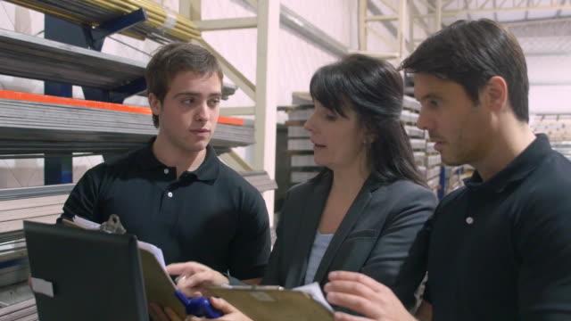 vídeos y material grabado en eventos de stock de trabajadores discutiendo sobre laptop en almacén - gerente de cuentas