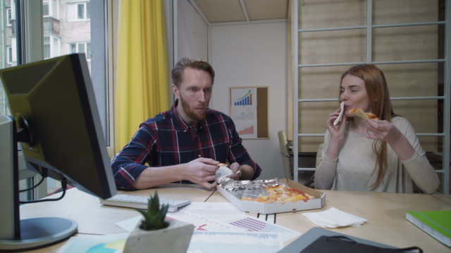 Workers eat pizza in the office at the workplace video