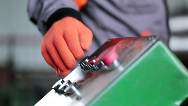 Worker's hand controls the press at the factory. Worker's hand presses the buttons of the control panel of the press at the factory production line worker stock videos & royalty-free footage