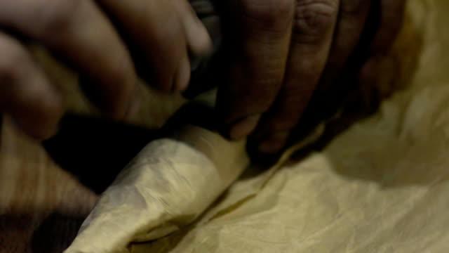 mani del lavoratore che avvolgono un dettaglio in un foglio - full hd format video stock e b–roll