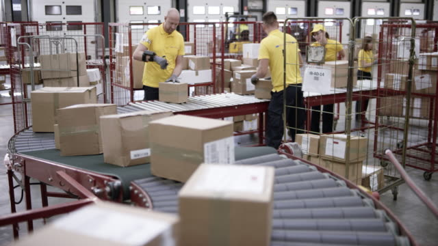 LD Workers in a warehouse putting packages on the conveyor belt Wide locked down shot of workers putting packages ion the conveyor belt in the warehouse. Shot in Slovenia. production line worker stock videos & royalty-free footage
