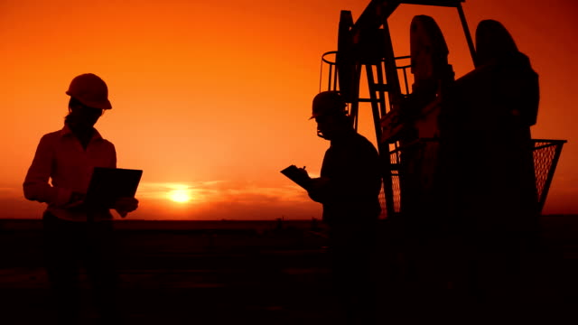 Workers in an Oilfield at Sunset