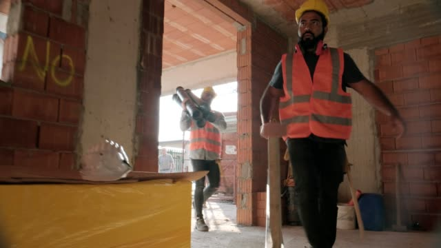 stockvideo's en b-roll-footage met werknemers in de bouw-site met behulp van tools en zware apparatuur - ladder