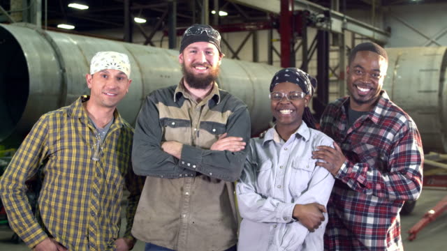 Workers in metal fabrication shop A group of four multi-ethnic workers in a metal fabrication shop, on the factory floor, large metal objects in the background. A bearded man standing in the foreground is joined by his coworkers, including an young African-American woman. They smile and look at the camera. focus on foreground stock videos & royalty-free footage