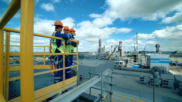 stockvideo's en b-roll-footage met werknemers in de productie van planten als team bespreken, industriële scène in achtergrond - chemische fabriek