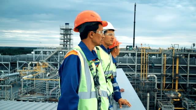 stockvideo's en b-roll-footage met werknemers in de productie van planten als team bespreken, industriële scène in achtergrond - raffinaderij