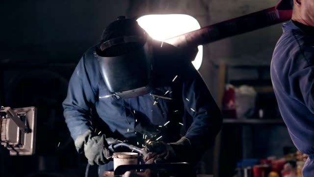 Workers in protective workwear at mechanical hangar. Workman in welding helmet joins two metal pieces together. Dangerous work. Workers in protective workwear at mechanical hangar. Workman in welding helmet joins two metal pieces together. Dangerous work production line worker stock videos & royalty-free footage