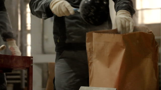 workers in respirators pour mix from paper bags in warehouse Male workers in grey uniform and respirators pour dry mixture from paper bags in production plant warehouse cement stock videos & royalty-free footage