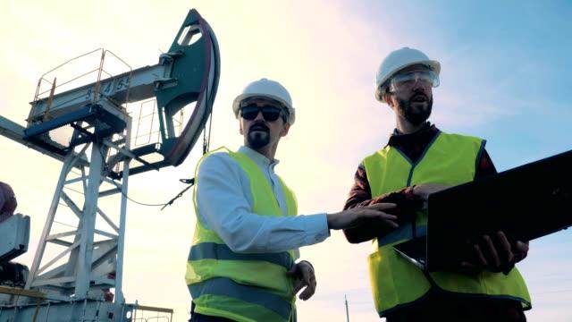 arbetare i uniform kontrollera olje tornen på ett fält, närbild. - pipeline bildbanksvideor och videomaterial från bakom kulisserna