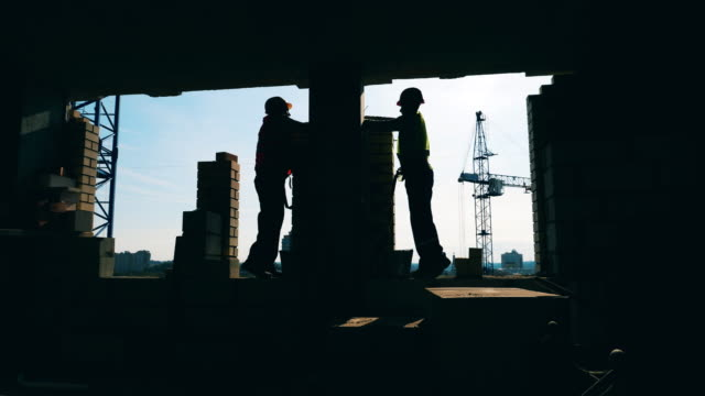 Workers in uniform laying bricks at a building site.
