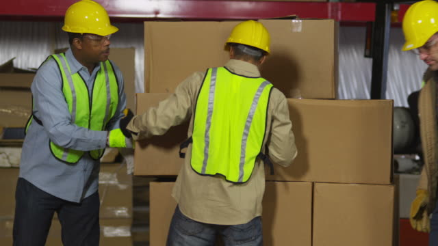 Workers in warehouse stacking boxes video
