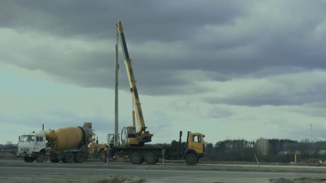 arbeiter installieren einen mast mit straßenlaterne mit autokran entlang der straße. baumaschinen, beton- oder zementmischer transport truck sind auf dem arbeitsgebiet. ingenieure richten laternenmast auf autobahn ein - unterordnung stock-videos und b-roll-filmmaterial