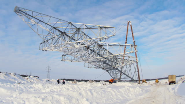 workers install high voltage line support pulling by mechanisms