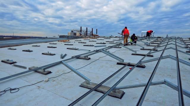 arbetare installera metallbas för solpaneler. konstruktion av ny sol gård under rörelse av moln på himlen. tidsinställd. - roof farm bildbanksvideor och videomaterial från bakom kulisserna