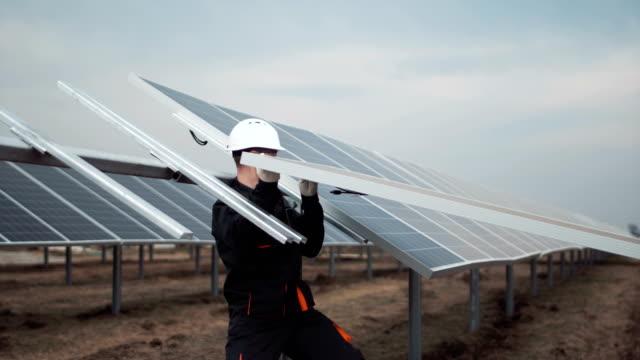 vídeos de stock e filmes b-roll de workers install the photovoltaic panel - equipamento solar