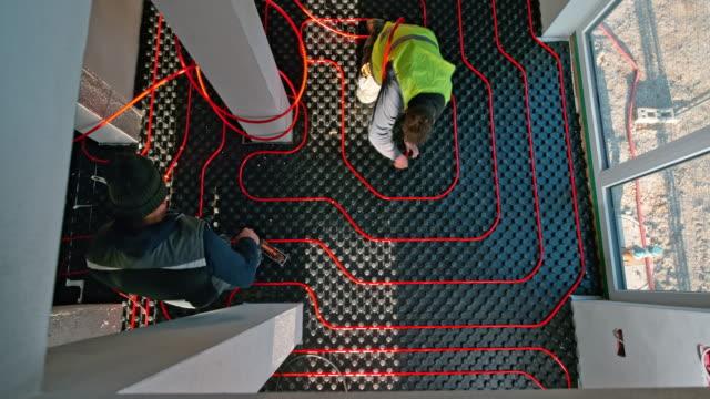 time-lapse arbetstagare om röda golvvärmerör - construction workwear floor bildbanksvideor och videomaterial från bakom kulisserna