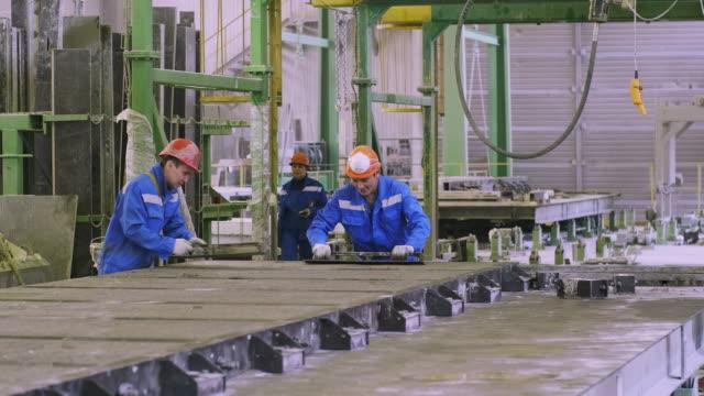 vídeos y material grabado en eventos de stock de trabajadores nivelando cemento a formas - brigada