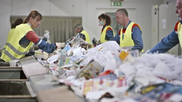 LD workers making last waste paper check on conveyor belt video