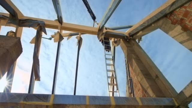stockvideo's en b-roll-footage met werknemers op het dak begeleiden de kraan houden de houten balken in de lucht - ladder