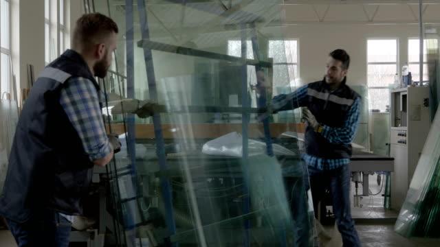 vídeos de stock e filmes b-roll de workers packaging glass sheets in warehouse - vidro