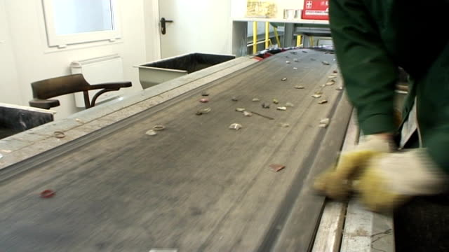 Workers picking out trash from cullet caried by conveyor belt video