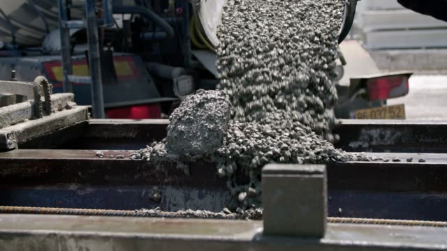 workers pouring concrete into large steel molds on a construction site - spranga video stock e b–roll